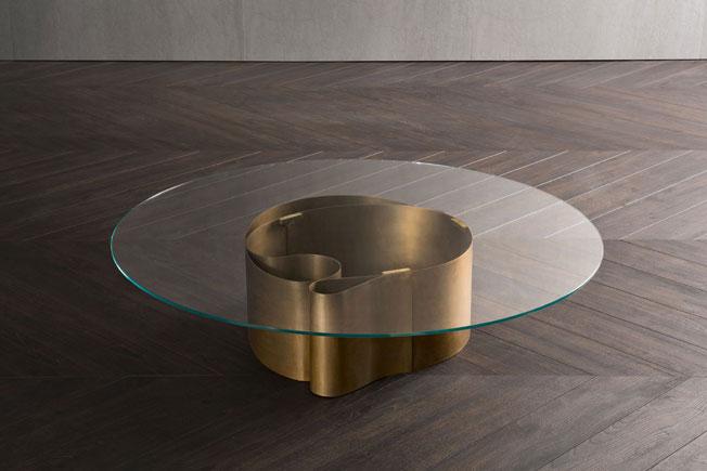 B-Wave, диз. Массимо Кастанья. Низкий столик, основание сформировано вручную: черненый латунный лист завернут волной. Круглая столешница из сверхсветлого или бронзированного стекла позволяет хорошо рассмотреть его скульптурную форму.